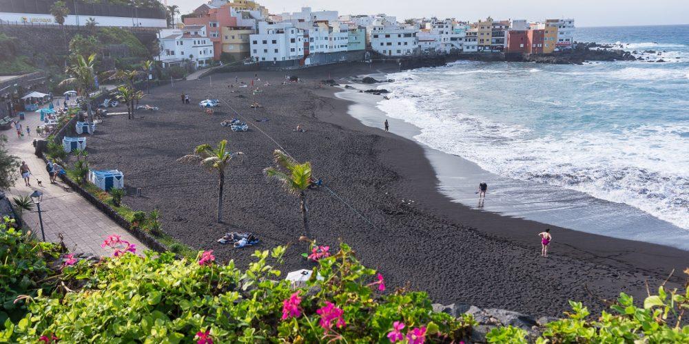 Foto de Puerto de la Cruz donde se puede ver la playa de arena negra y las casas al fondo