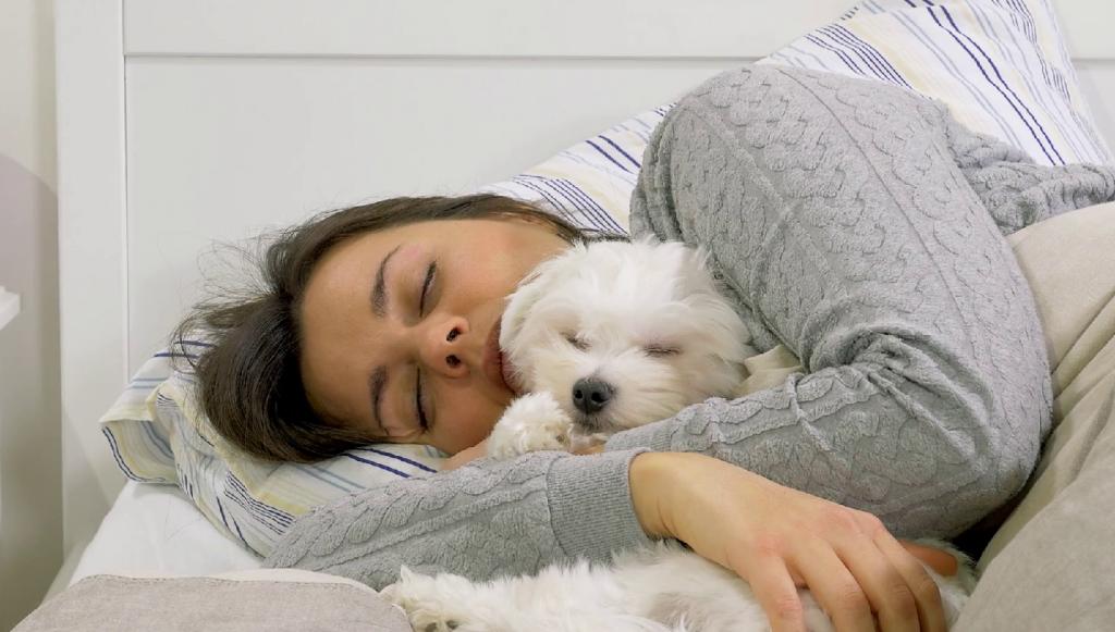Chica durmiendo con su cachorro en brazos