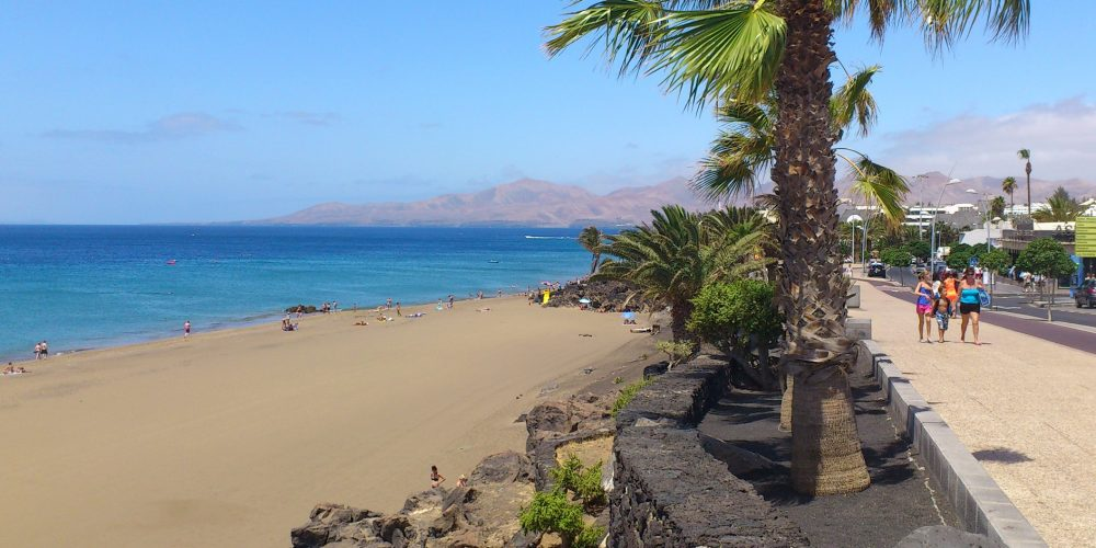 Foto de una playa de lanzarote con un paseo junto a la playa y palmeras.