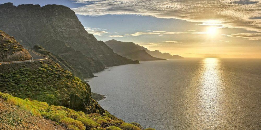 Foto de la carretera que hay a las afueras de Agaete donde se puede ver lo escarpados de los acantilados, el mar y el sol reflejado en el agua