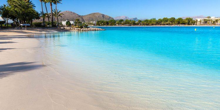 Foto de la playa de Alcudia donde se puede ver el color blanco de la arena y el color azul de las aguas