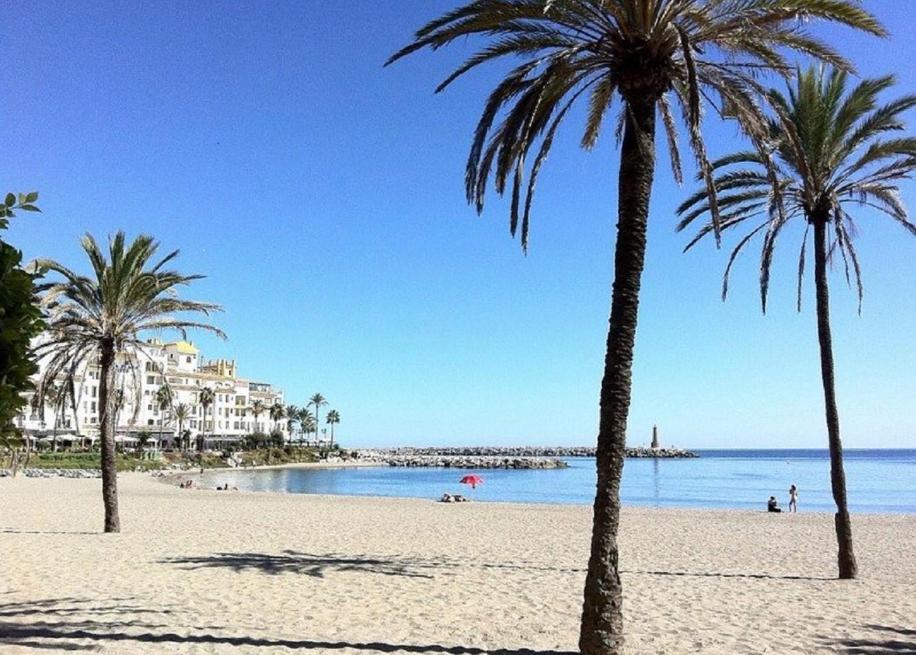 Foto de la playa de Marbella donde se ve lo blanca que es la arena y el mar de fondo