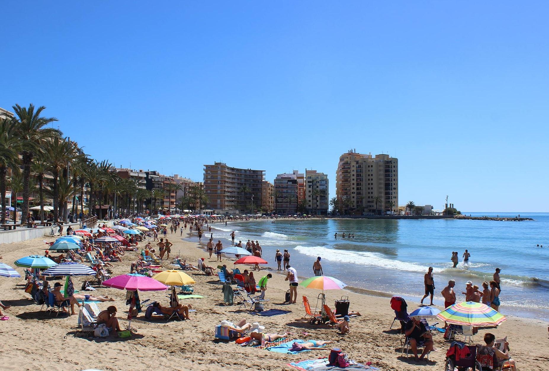Foto de la playa de Torrevieja un día soleado y con la gente disfrutando del mar con sus sombrillas