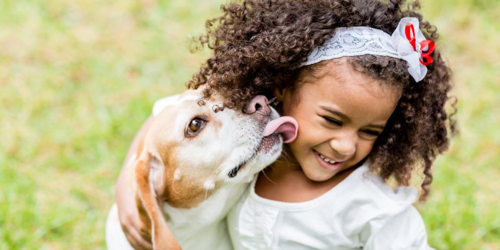 Niña jugando con un perro mientras este le lame en la cara