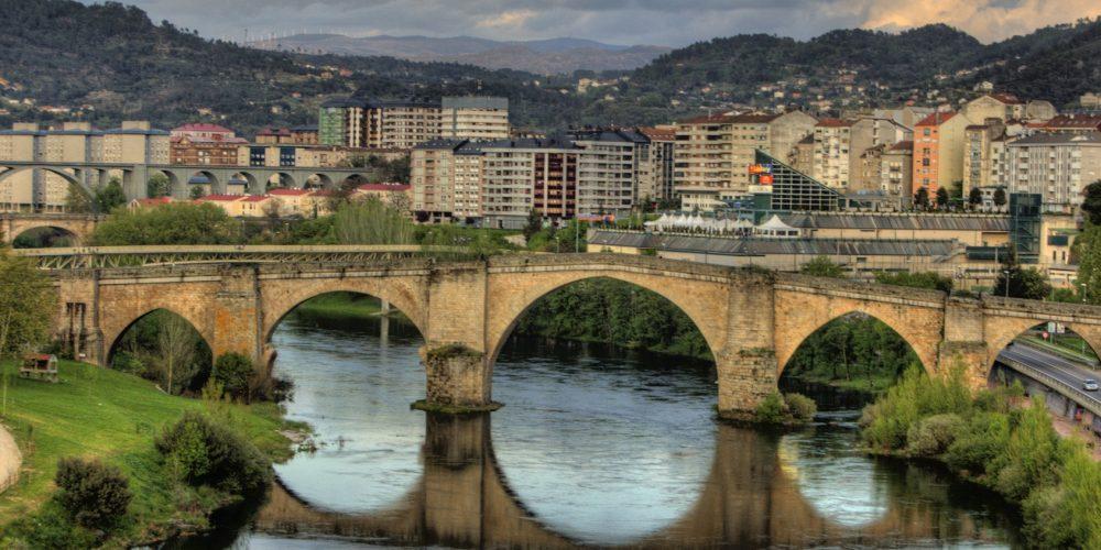 Foto de la ciudad de Ourense que se puede ver detrás del puente de piedra y que invita a visitar y pasear con tu perro