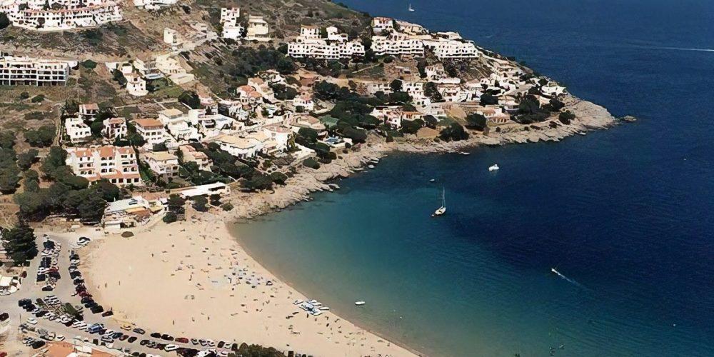 Foto de la playa de Torroella de Montgrí donde se puede ver la población al fondo de la playa sobre una pequeña colina sobre el mar