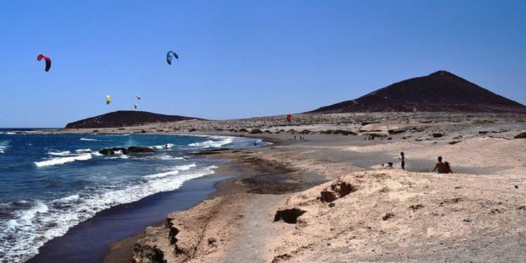 Foto de la playa del Médano con la Montaña Roja al fondo. Lugar perfecto para ir de vacaciones con tu perro