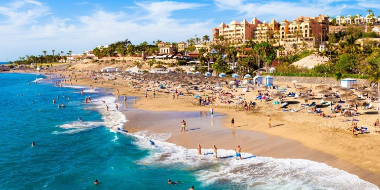 Foto de la playa de Adeje donde se puede ver la calidad de la arena, el color del mar azul turquesa y al fondo todos los alojamientos entre los que se encuentran algunos apartamentos que admiten perros GRATIS