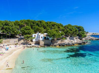 Playa de Cala Ratjada donde se puede ver el blanco de la arena y color transparente del agua donde además puedes encontrar un alojamiento para ir con tu perro