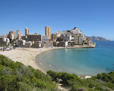 Vista desde la colina de la playa de Cala Finestrat y donde se puede ver el color blanco de la arena, las aguas cristalinas y los apartamentos al fondo