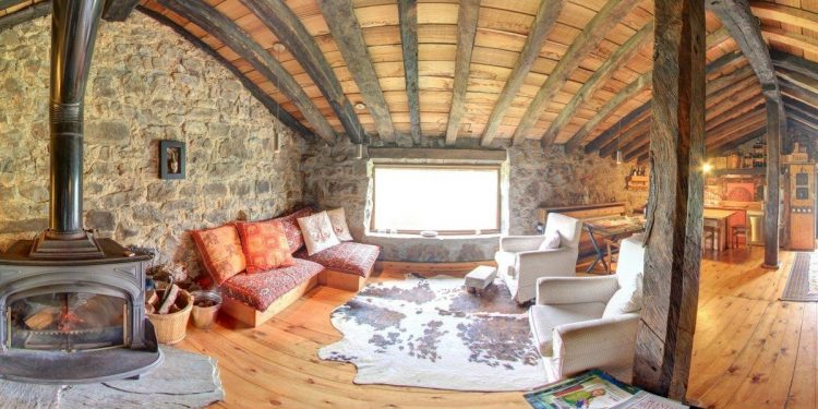 Foto del interior de una cabaña de auténtico lujo con materiales de piedra y madera con chimenea y decoración rústica