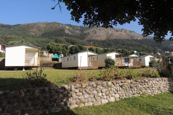 Foto desde lejos donde se ve un grupo de cabañas de madera