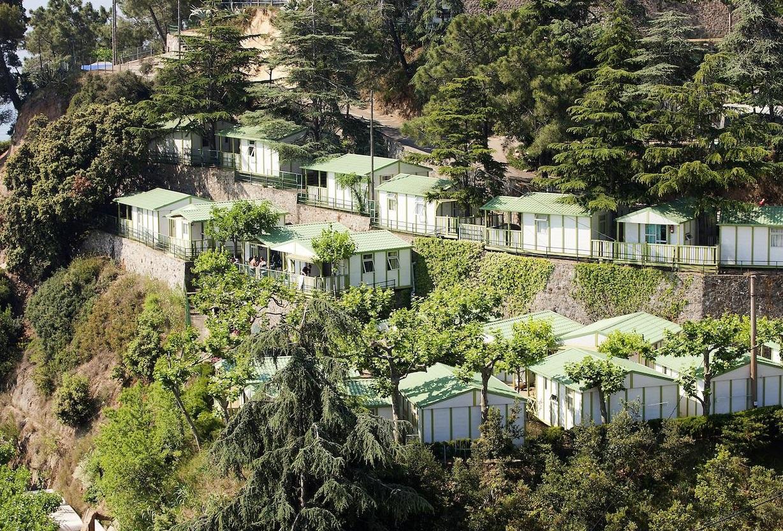 Foto desde el aire donde se ve en una colina un grupo de bungalows de madera