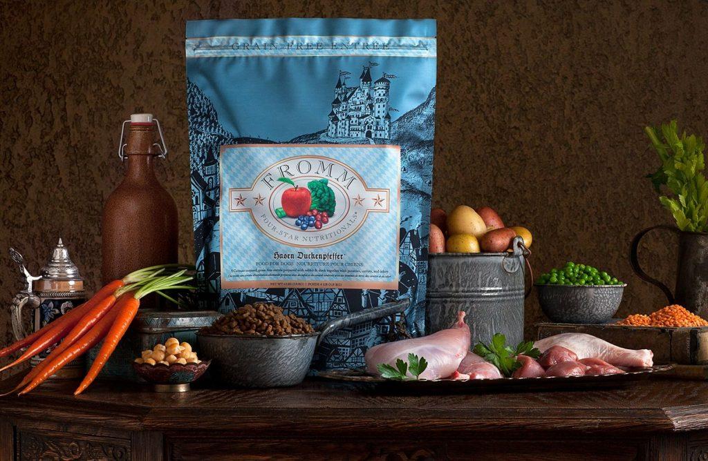 Foto de una bolsa de pienso para perros rodeado de ingredientes naturales