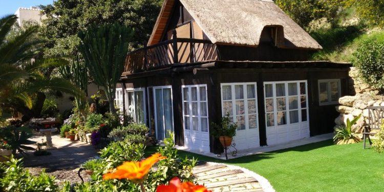 Foto del exterior de Alojamientos Cortijo Grande donde vemos lo encantadora de la casa y los bonitos jardines de este lugar que admite perros