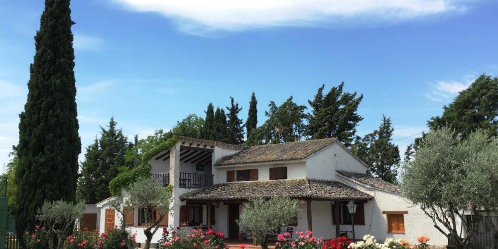 Foto del exterior de la La Casona del Cipres donde se puede ver el cesped y los jardines de esta bonita casa rural que admite perros cerca de Madrid