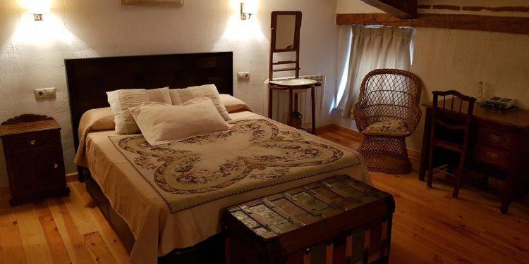 Interior de uno de los apartamentos que admiten perros en Cuenca con suelos de madera y techos rústicos